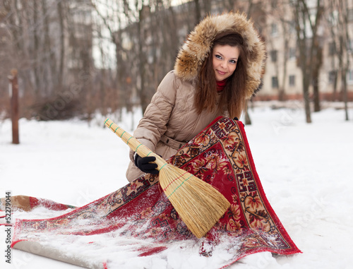Smiling woman cleans red carpet with snow