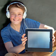 Cute boy with earphones showing blank tablet screen.