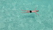 Teenager has a rest on turquoise transparent water of ocean