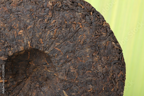 Disc of chinese puer tea on green background