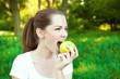 Close up portrait of girl bites an apple outdoor