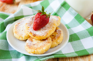 cheese pancakes with powdered sugar and strawberries