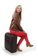 Girl sitting on a suitcase, isolated on white background
