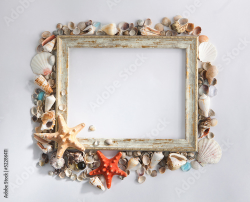 Shabby picture frame with blank space inside and shells, on whit