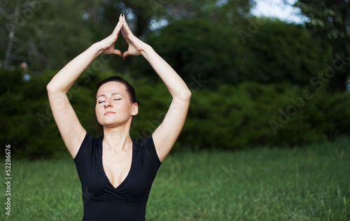Young woman doing yoga exercises outdoors