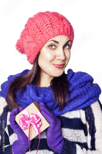 Happy woman in winter clothing holding Christmas present box