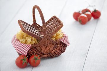 Cesta de mimbre con tomates cherry y pasta de espirales
