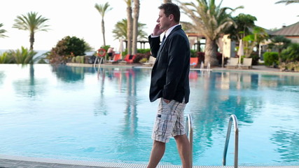 Young businessman talking on cellphone in luxury resort