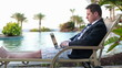 Businessman with laptop on sunbed by the pool