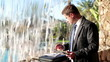 Businessman with tablet and documents stand by the waterfall