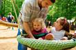 Junge Vater mit zwei Kindern auf der Schaukel