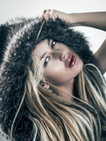 fashion portrait of attractive blonde woman in fur coat hood