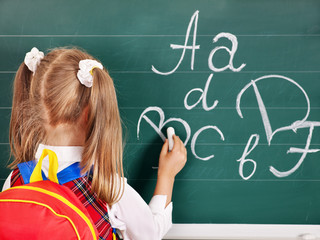 Schoolchild writting on blackboard