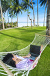 Asian girl work in hammock with laptop at beach