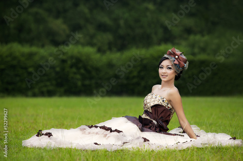 Beautiful woman in formal dress gown at park
