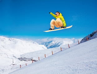 Cute snowboarder man jumping on ski resort