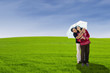 Cheerful couple with umbrella on green field