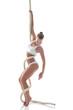 Pretty slim gymnast posing on rope in studio