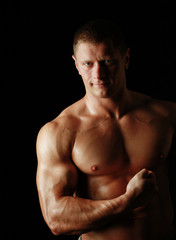 Healthy muscular young man. Isolated on black background
