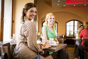 Hübsche junge Frauen beim Kaffeetrinken