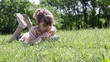 little girl lying on grass and playing with tablet pc