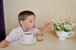 little boy drinks tea and eats with a spoon and honey on the tab