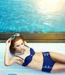 Summer . Beautiful young woman at a pool