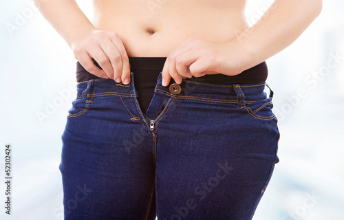Woman zipping tight jeans, obesity and overweight concept