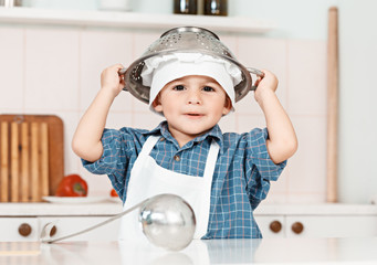 little boy plays a chef cooking utensils