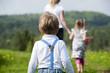Kleiner Junge läuft Mutter und Schwester nach