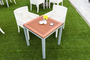 Tropical wooden dinning table on green grass