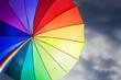 Rainbow umbrella on stormy sky background
