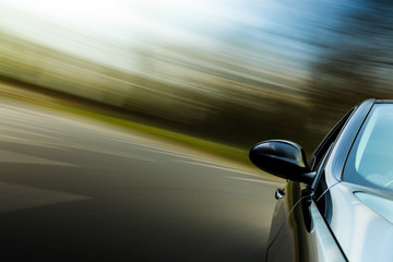Front side mirror view of black car with heavy blurred motion.