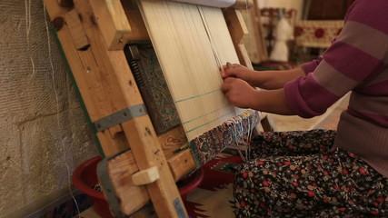 Woman weaving a carpet