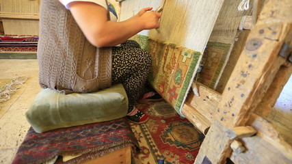 Woman weaving a carpet