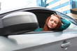 Woman in a car, looking into car side mirror