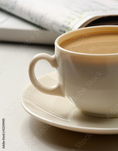 cup near newspapers
