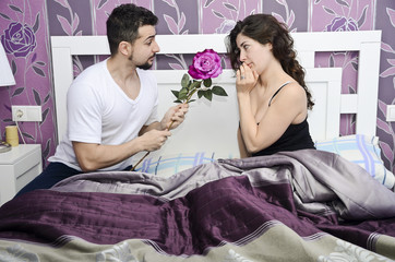 A rose for reconciliation, couple in vintage bedroom.