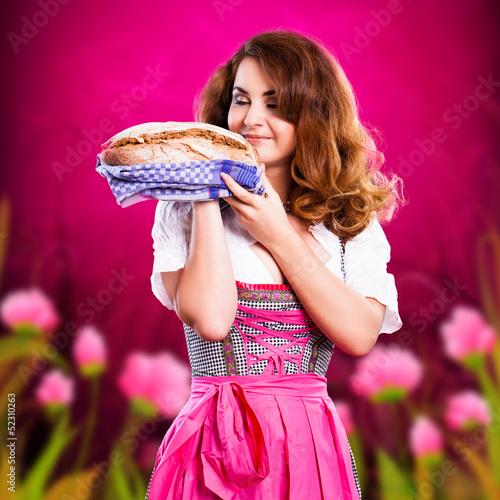 junge Frau im Dirndl bietet ein Brot an