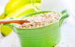 Oat flakes in the green bowl with banana and milk