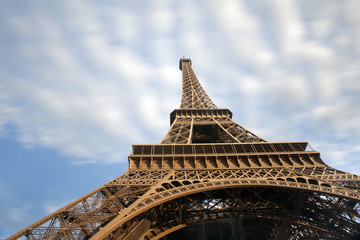 Eiffel tower detail with moving clouds on blue sky, Paris