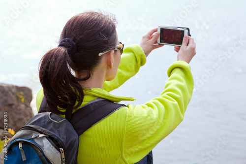Woman hiker taking a photo  by smartphone