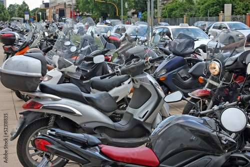 many scooters and motorcycles parked in road car park