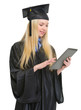 Happy young woman in graduation gown using tablet pc