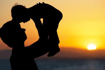 Папа и маленький сын - силуэты на пляже на закате