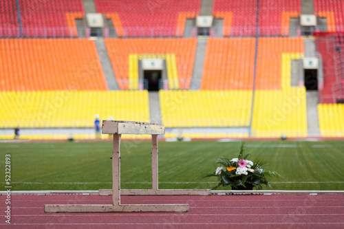 Barrier and beautiful flowers on the track stadium.
