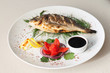 Grilled fish with tomato, herbs, onions and lemon