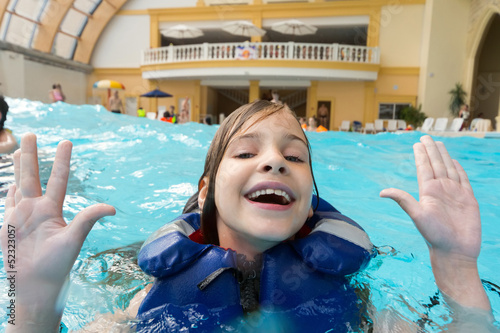 Happy girl in lifejacket in water park with his hands up.