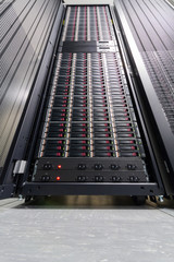 Data server in big rack with multiple hard drives.