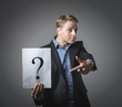 Young businessman holding  question mark